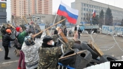 Pro-Russian activists reinforce their barricade outside the regional Security Service building in the eastern city of Luhansk on April 10.