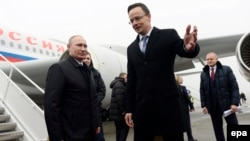 Russian President Vladimir Putin (left) is welcomed by Hungarian Foreign Minister Peter Szijjarto at the Liszt Ferenc International Airport in Budapest on February 2.