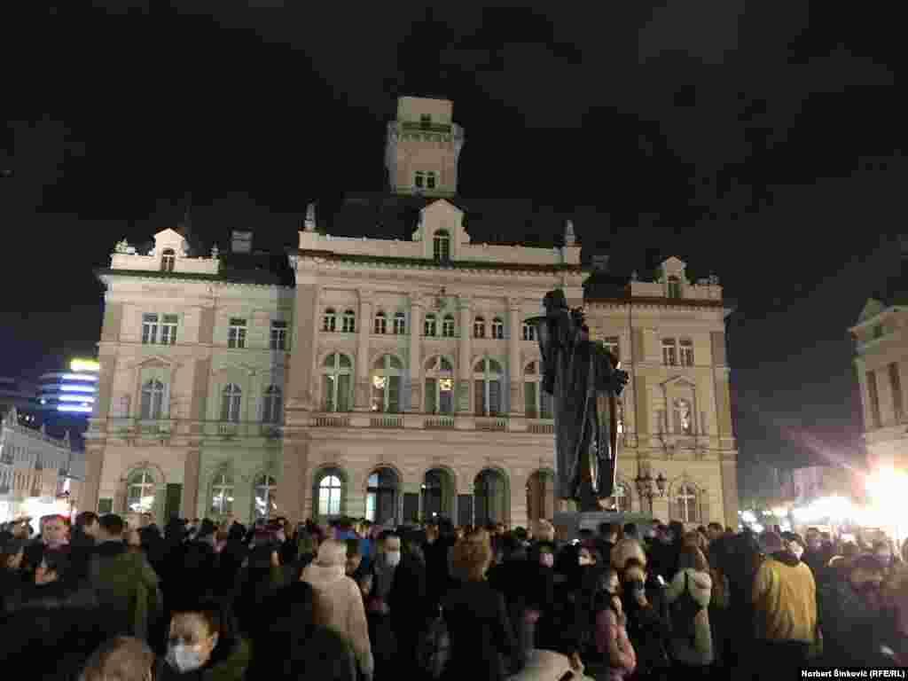 Građani se okupljaju na Trgu slobode u centru Novog Sada.Ukrasna javna rasveta je ugašena na Gradskoj kući a zastave su spustene na pola koplja.