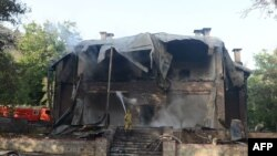 FILE: A Pakistani firefighter extinguishes a blaze which gutted a historical building in Balochistan's Ziarat region in 2013.