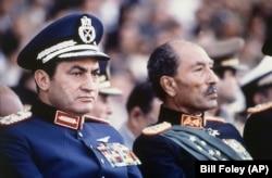 Вице-президент Египта Хосни Мубарак (слева) и президент страны Анвар Садат (справа) на военном параде. Каир, 6 октября 1981 года. Через несколько минут Садат будет убит