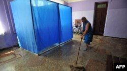 A woman mops the floor of a polling station ahead of the upcoming Ukrainian presidential election in the village of Oktyabr village in the Donetsk region on May 22.