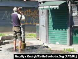 Бездомний чоловік чепуриться біля колонки