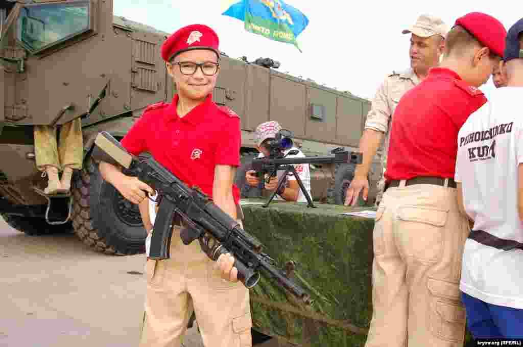 Мальчик в очках с автоматом на выставке стрелковых вооружений