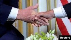 Ръкостискане. Лявата ръка е на Доналд Тръмп, дясната - на Еманюел Макрон. Двамата се срещнаха в Нормандия, където в четвъртък бяха отбелязани 75 години от дебаркирането на съюзниците по време на Втората Световна война.