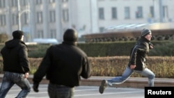 Belarusian plainclothes police chase a protester on Independence Square in Minsk after he pelted eggs at a statue of Lenin.