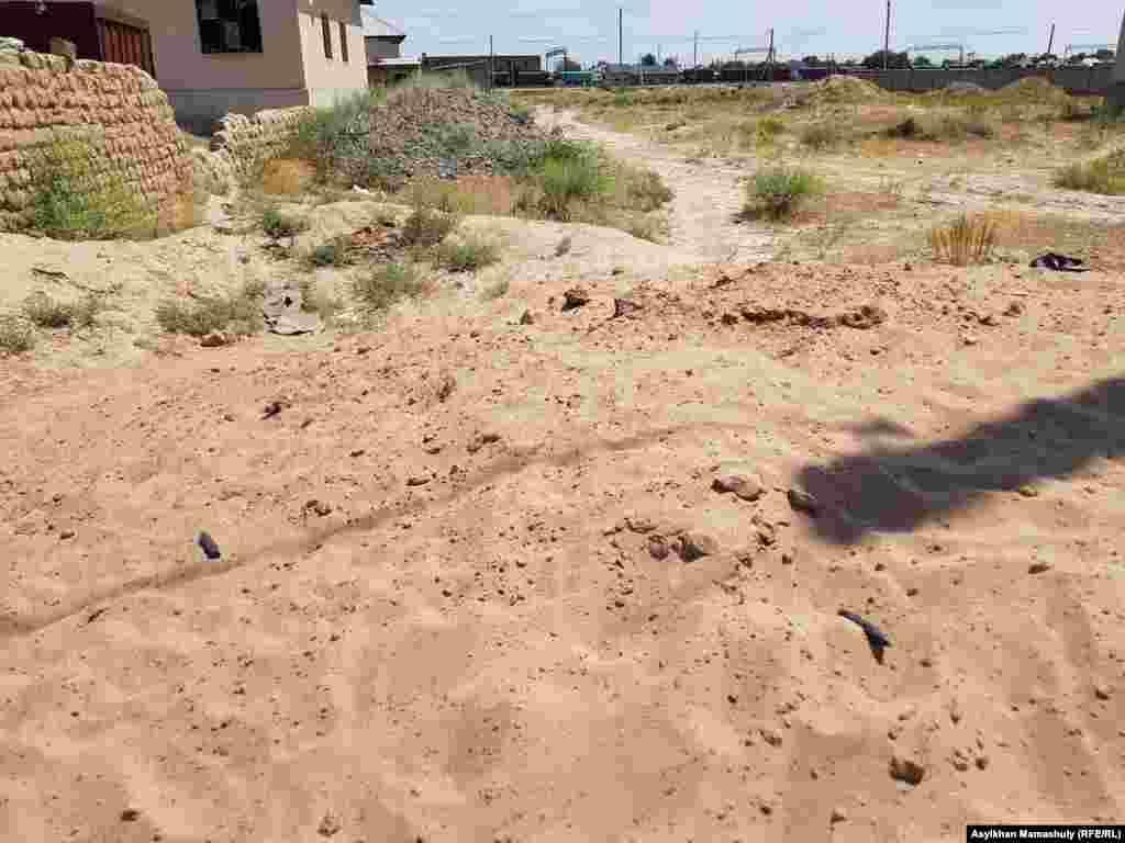 Үй алдындағы үйілген құмда екі оқ көрінеді. Арыс, Түркістан облысы, 29 маусым 2019 жыл.