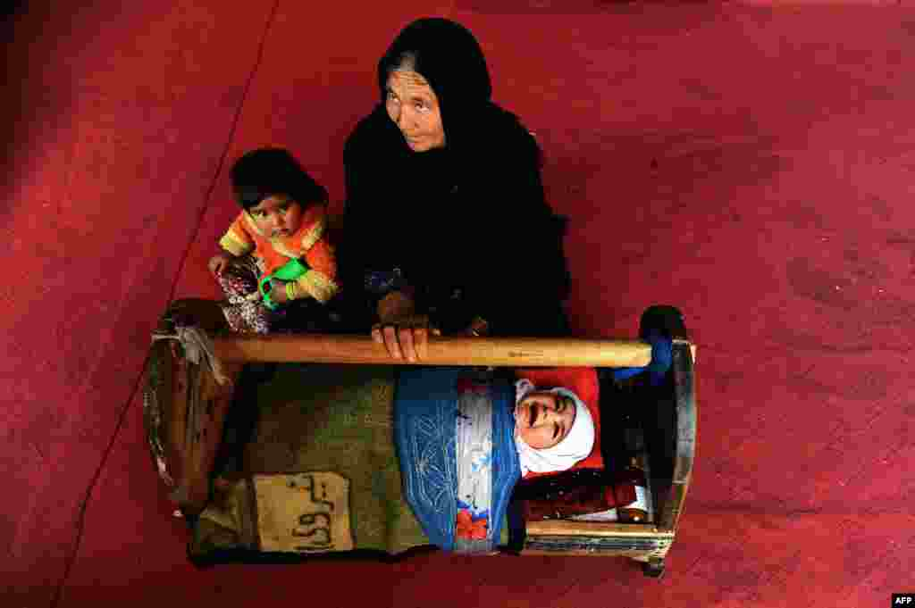 An Afghan woman rocks the cradle of her child at their house on the outskirts of Herat. (AFP/Aref Karimi)