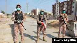 Soldiers wearing facemasks stand guard on road leading to a quarantine faciltity (R) for people returning from Iran via the Pakistan-Iran border town of Taftan to prevent the spread the coronavirus in Sukkur, a city in southern province of Sindh.