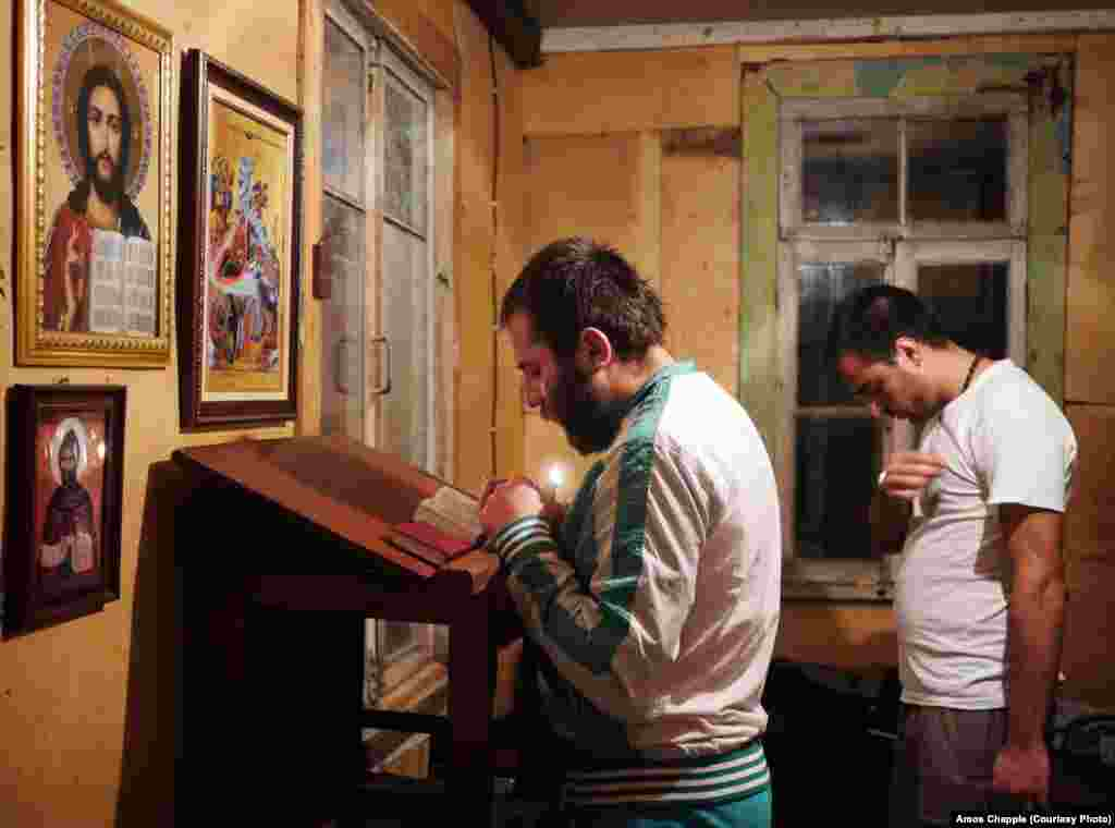 "Sergo Mikhelidze (left) and Irakli Kurashvili pray in their dormitory at the base of the pillar. Sergo worked in a factory until being laid off and is considering life as a priest or monk. He will stay at the monastery for three months to see if he is strong enough to commit to the life of a holy man. When asked what he has trouble avoiding in the outside world, he says: ""I just can't seem to stay away from girls."""