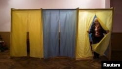 A staff member of a local community center, converted to a polling station, walks out of a voting booth in the Ukrainian village of Novotroits'ke, south of the pro-Russian rebels stronghold of Donetsk on October 23.