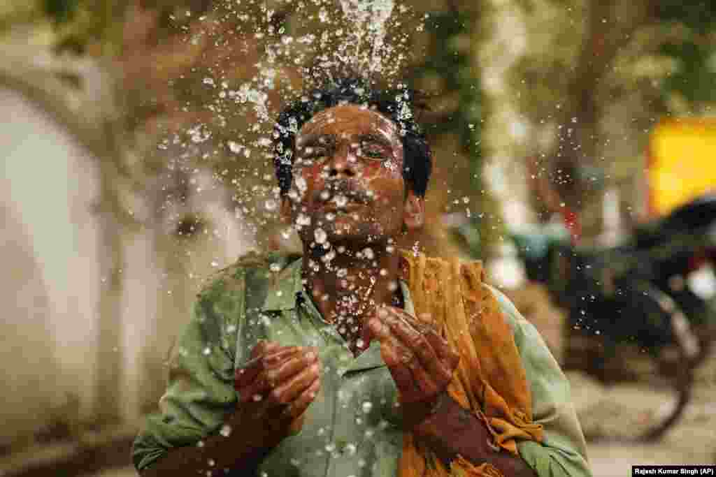 An Indian worker splashes water on his face on a hot summer afternoon in Prayagraj, Uttar Pradesh, India. Severe heatwave conditions are sweeping north and western parts of India with maximum temperature soaring to 48 degrees Celsius in some areas. (AP/Rajesh Kumar Singh)