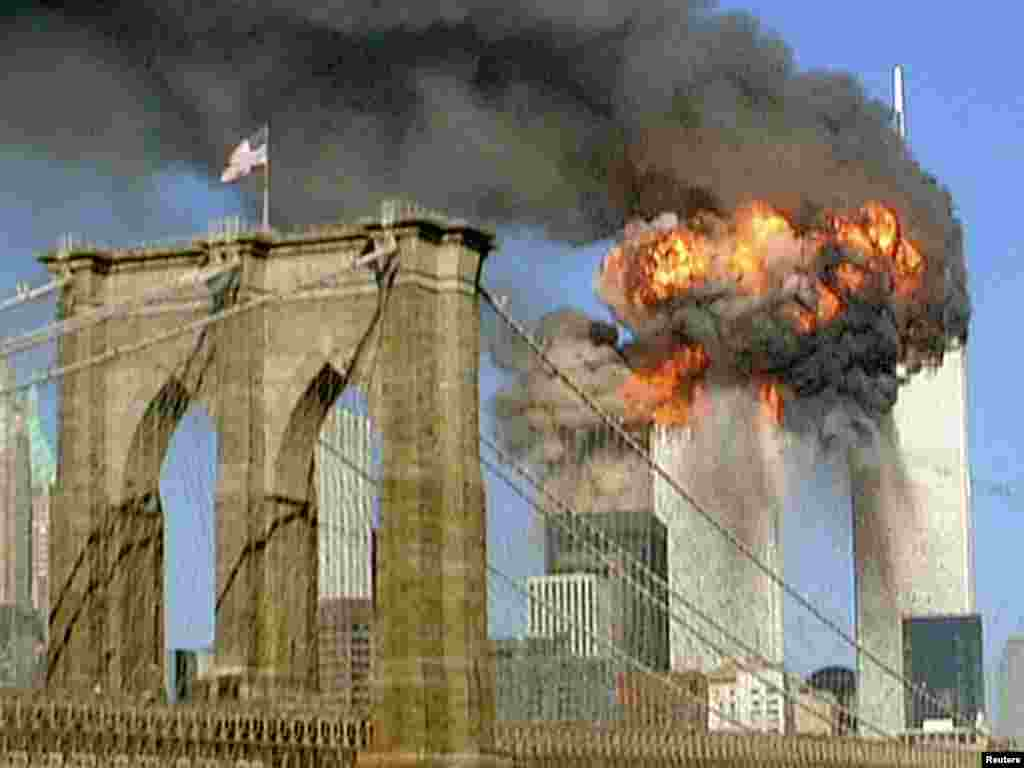 The World Trade Center towers burn behind the Brooklyn Bridge on September 11, 2001.