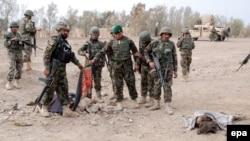 Owgan goşunynyň esgerleri öldürilen jeňçileriň jesediniç ýanynda durlar. Kandahar, 20-nji ýanwar, 2014