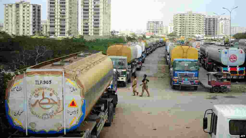 Men walk past fuel tankers, used to transport fuel to NATO forces in Afghanistan, parked near oil terminals in the Pakistani port city of Karachi.