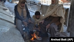 People sit around a fire to warm themselves after a heavy snowfall in Quetta on January 13.