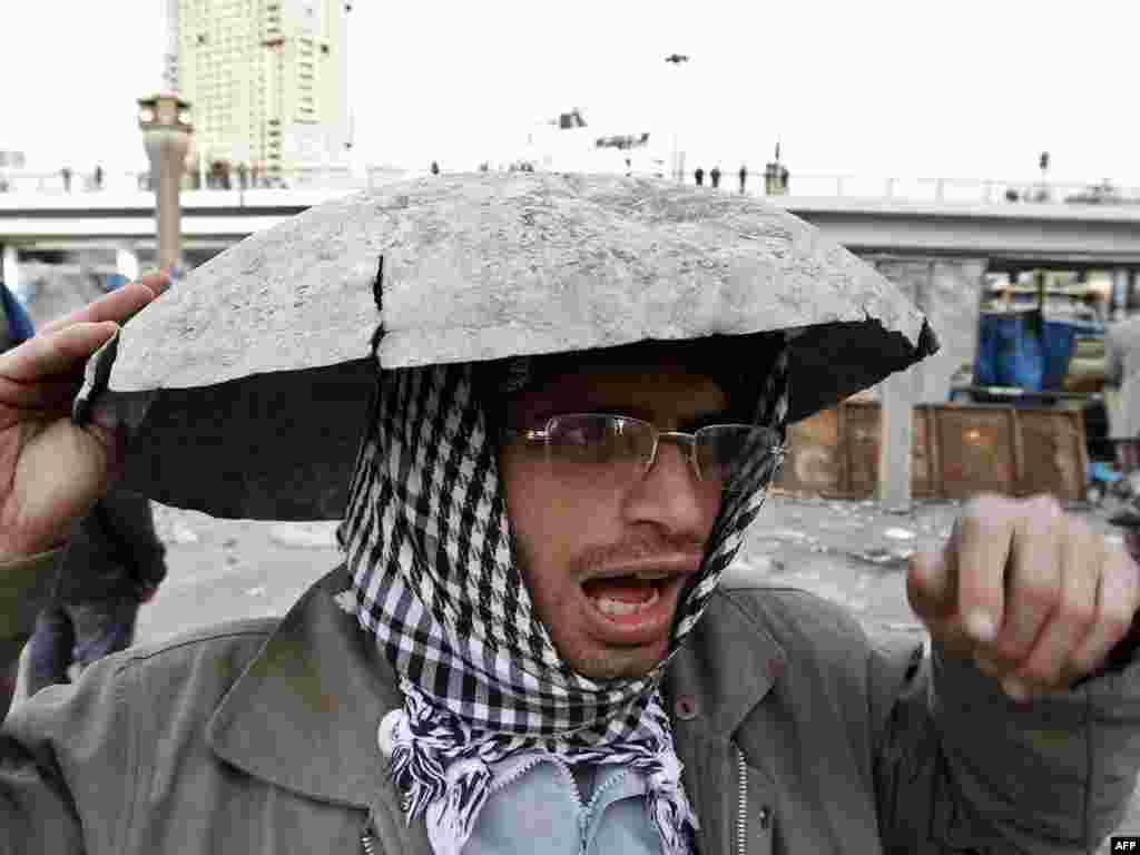 An antigovernment demonstrator covers his head.