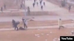 Вооруженные полицейские бьют лежачего на земле человека. Скриншот с любительской видеозаписи, сделанной из окна жилого дома Жанаозена 16 декабря 2011 года.