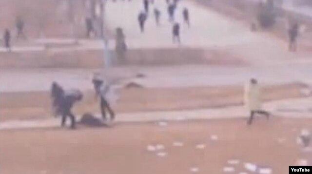 Жаңаөзен оқиғасы кезінде оқ тиіп қаша алмай қалған азаматты полиция сабап жатыр. Интернетке жарияланған видеодан скриншот. Жаңаөзен, 16 желтоқсан 2011 жыл.