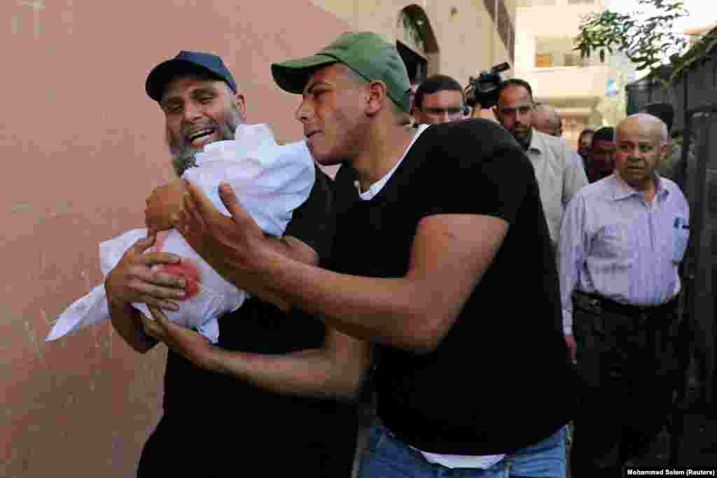 Relatives carry the body of 4-month old Palestinian girl Maria al-Ghazali during her funeral in Gaza City. A cease-fire deal ended the deadliest fighting between Israel and Palestinian militants in the West Bank and Gaza Strip since a 2014 war. A two-day outbreak of violence killed 25 people in Gaza, both militants and civilians, and four civilians in Israel. (Reuters/Mohammed Salem)