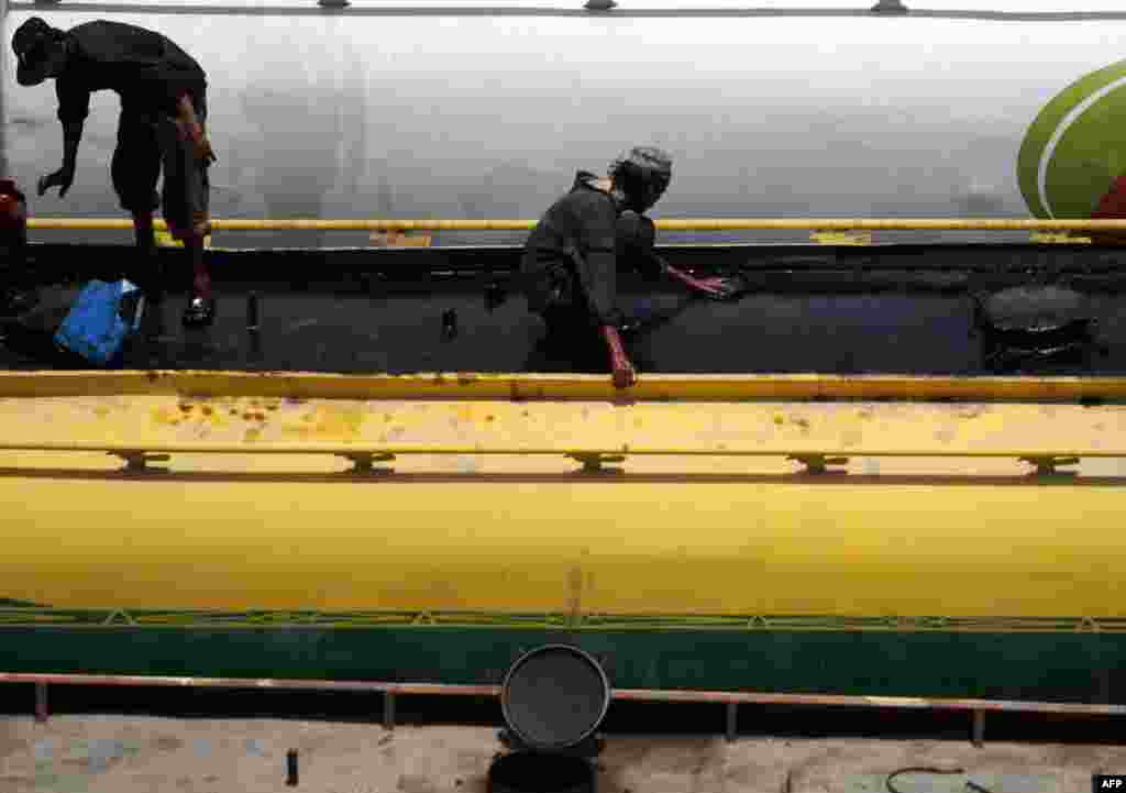 Laborers clean a tanker truck in Karachi ready to transport NATO goods on May 15.