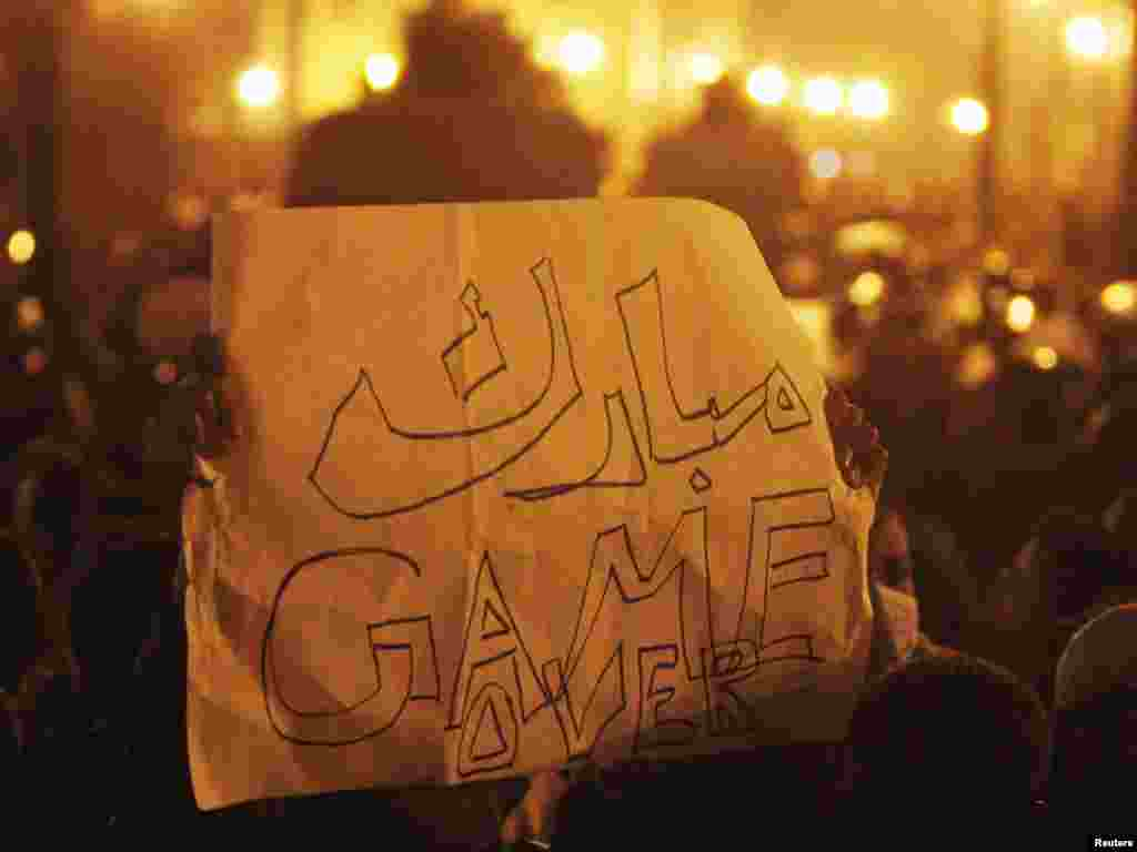 A protester holds a banner reading ''Mubarak: Game Over'' in downtown Cairo.