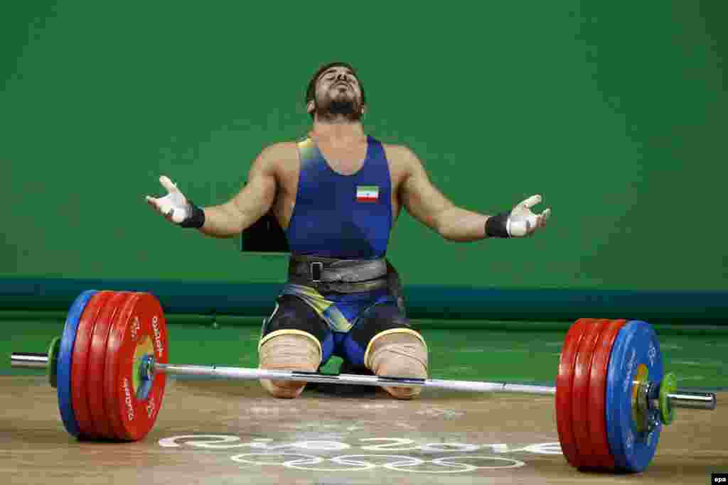 Kianoush Rostami of Iran reacts after setting a new Olympic record during the men's 85-kilogram Group A category final.