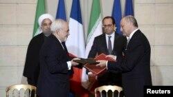 Хасан Роугані (позаду л) і Франсуа Олланд (позаду п) на церемонії підписання угод; попереду голови МЗС Ірану Могаммад Джавад Заріф (л) і Франції Лоран Фаб'юс (п), Париж, 28 січня 2016 року