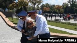 Полицейские уводят женщину с площади в Алматы. 9 мая 2019 года.