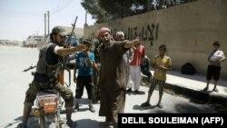 Боец СДС указывает гражданским лицам безопасный путь в городе Манбидж в ходе недавних боев