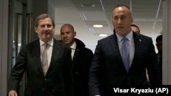 Kosovo's prime minister, Ramush Haradinaj (right), walks with the European Union's enlargement commissioner, Johannes Hahn, upon his arrival in Pristina on December 3.