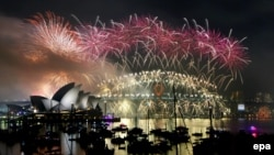 A massive fireworks display lights up the sky above the Sydney Opera House and the Sydney Harbour Bridge in Australia.