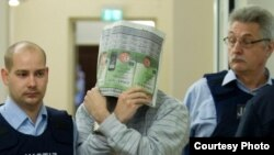 Ҳуссам полиция назоратида суд залига олиб кирилаётган пайт, Кобленц, 2012 йил 23 март.