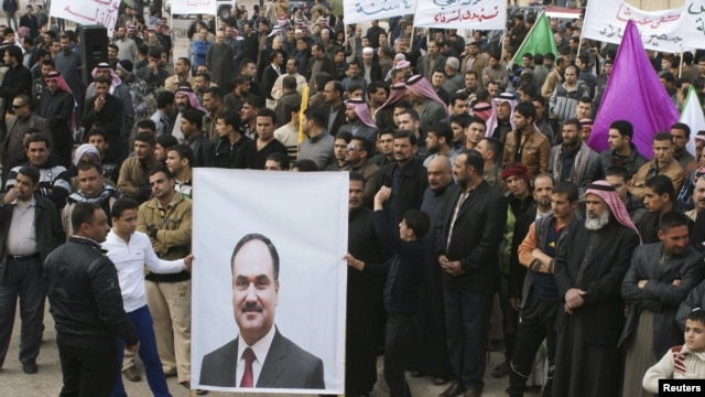 Protesters hold a poster of Iraqi Finance Minister Rafia al-Issawi during a demonstration calling for Prime Minister Nuri al-Maliki's resignation in the western city of Falluja in December.