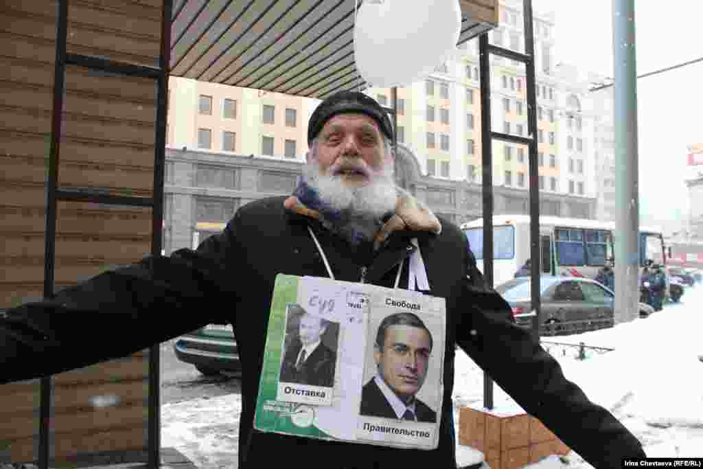 "An elderly demonstrator wears a sign with pictures of Prime Minister Vladimir Putin and jailed ex-tycoon Mikhail Khodorkovsky. The former is accompanied by the words ""Trial -- Resignation;"" the latter reads ""Government -- Freedom."""