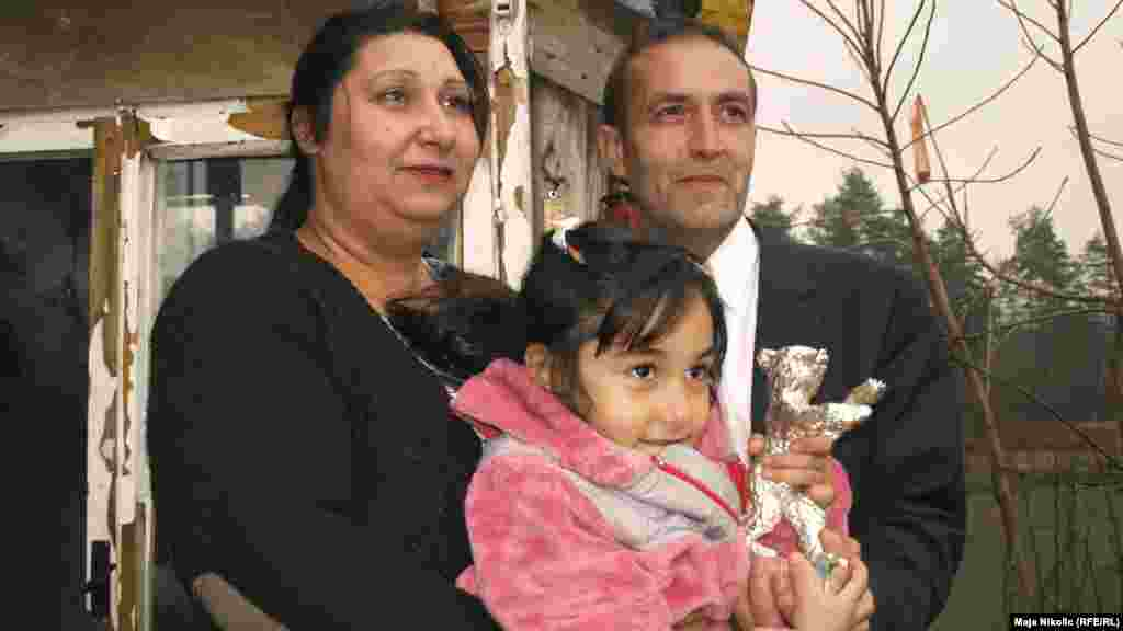 Mujic, Alimanovic, and their daughter pose in front of their house.