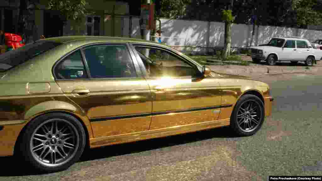 A gold-colored sedan is one of the ostentatious cars on the streets of Grozny.