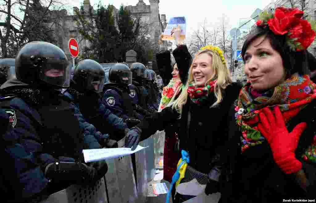 Ukrainian women, dressed in traditional costume, chat with riot police.