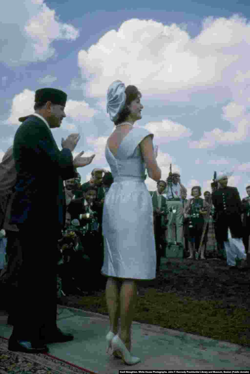 Jacqueline Kennedy and President Mohammad Ayub Khan watch the parade. The first lady later complimented Khan on his traditional fur hat, and the president gifted it to her.