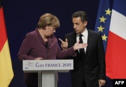 France -- President Nicolas Sarkozy and German Chancellor Angela Merkel talk to each other prior to holding a joint press conference following crisis talks with Greek Prime Minister in Cannes, 02Nov2011