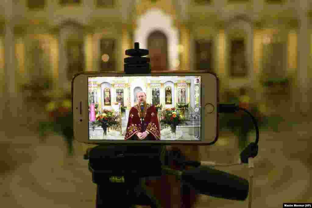 Руски православен свештеник им зборува на верниците за време на преносот во живо во една празна московска црква на 19 април.