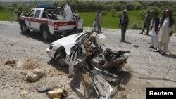Afganët i shikojnë mbeturinat e një makine pas një eksplodimi të mëparshëm në provincën Laghman