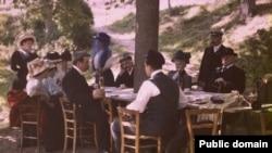 «Люмьеры: семейный обед. Луи Люмьер — сидит у дерева, Огюст, в фуражке, — стоит возле стола», 1910 год