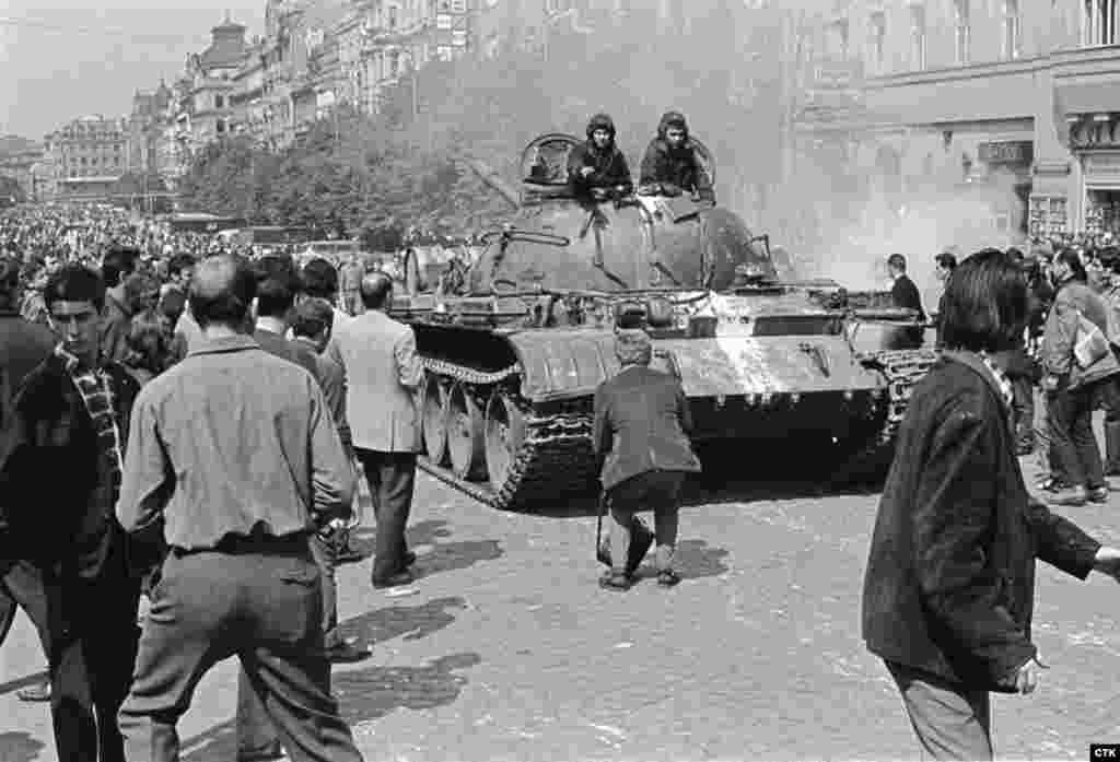 A photographer approaches a Soviet tank to take a photo on central Wenceslas Square.