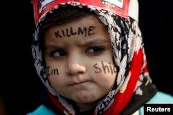 """Шиит қыз Кветтадағы хазаре қауымына жасалған шабуылдарға қарсы наразылық акциясына """"Мені өлтір, мен де шиитпін"""" деген жазумен шықты. Пәкістан, 19 ақпан 2013 жыл."""