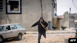 Человек бежит в укрытие во время вчерашнего обстрела Мисураты войсками Муамара Каддафи