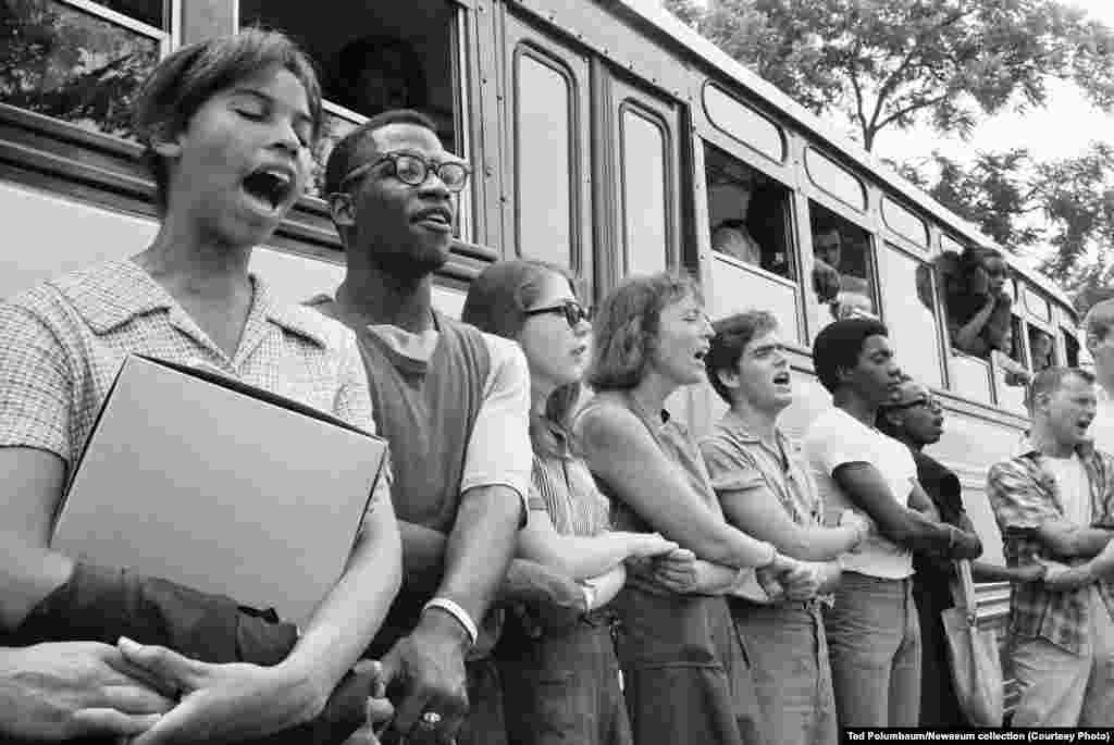 Student activists join hands and sing as they prepare to leave Ohio to register black voters in Mississippi in 1964. The voter registration campaign was known as Freedom Summer.