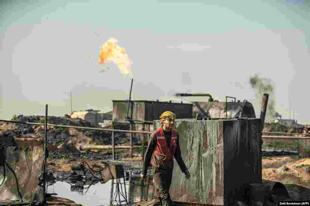 A Syrian worker walks at a primitive oil refinery in the countryside in Syria's northeastern Hasakeh Province near the Turkish border. (AFP/Delil Souleiman)