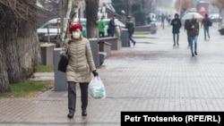 Женщина идет по улице в Алматы. 18 марта 2020 года.
