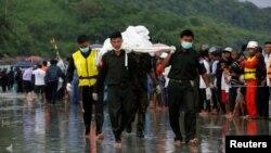 Ushtarët duke i bartur trupat e pajetë të gjetur nga aeroplani ushtarak i zhdukur dje në Birmani
